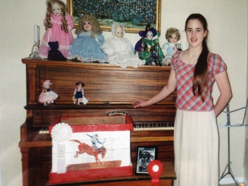 One thing we did continue doing were her private art lessons. Here she's pictured with her ribbons she earned in photography and painting. The wooden box she found in the old barn and painted for her little brother. The photo is, of course, of her dog.